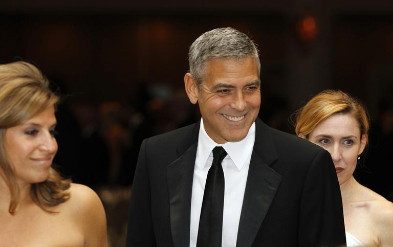 George Clooney, center, attends the White House Correspondents' Association Dinner in April in Washington. President Obama's campaign fundraiser at George Clooney's house last month raised $15 million. (AP)