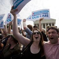 Claire McAndrew of Washington, left, and Donny Kirsch of Washington celebrate outside the Supreme Court in Washington, after a the court's ruling on health care, Thursday. (AP)