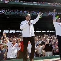 Former Boston Red Sox players Kevin Millar, left, and Pedro Martinez lead the fans in a toast at Fenway Park in Boston, Friday, April 20, 2012, during a celebration of the 100th anniversary of the first regular-season game at the ballpark. (AP)