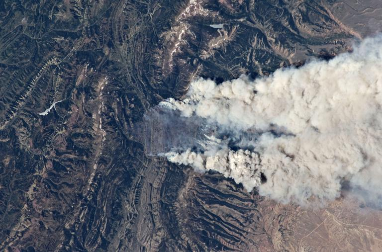 In this Wednesday June 27,2012 photo released by NASA showing wild fires burning at the south end of the Wyoming Range in southwestern Wyoming taken aboard the International Space Station, 240 miles above earth. These particular fires, of unknown cause, are burning at the south end of the Wyoming Range in southwestern Wyoming, and have affected 17,000 acres. (AP)