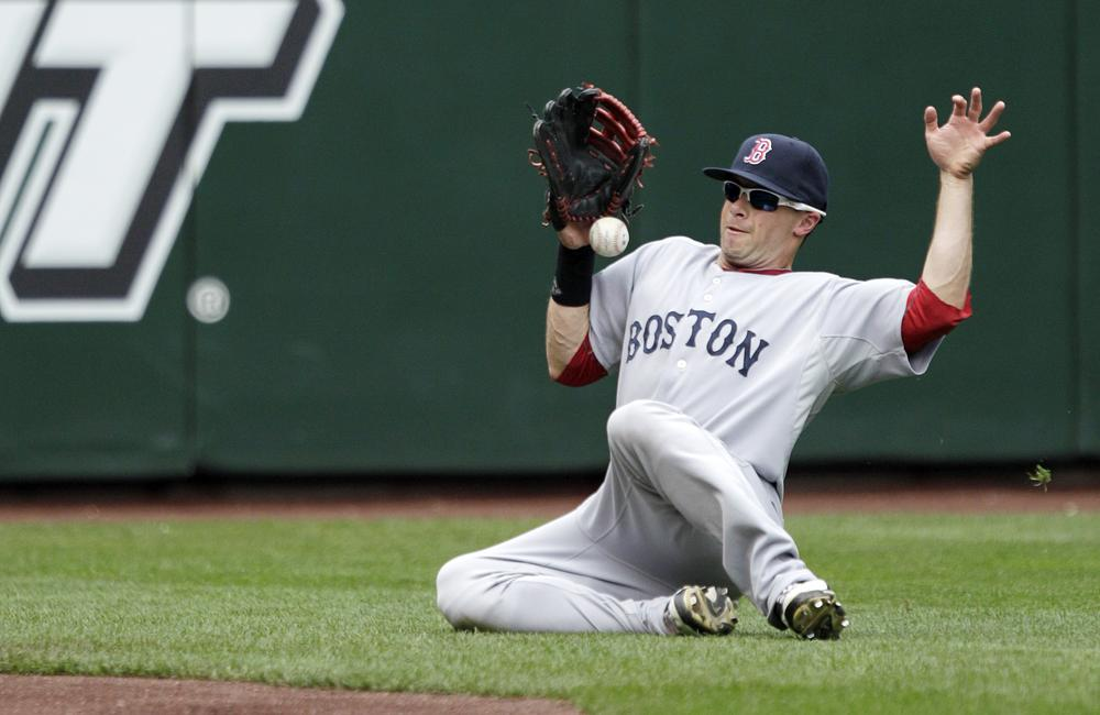 Red Sox left fielder Daniel Nava slides as he fields a double hit by Mariners' Justin Smoak, in the ninth inning of yesterdays game, in Seattle. The Red Sox beat the Mariners, 2-1. (AP)