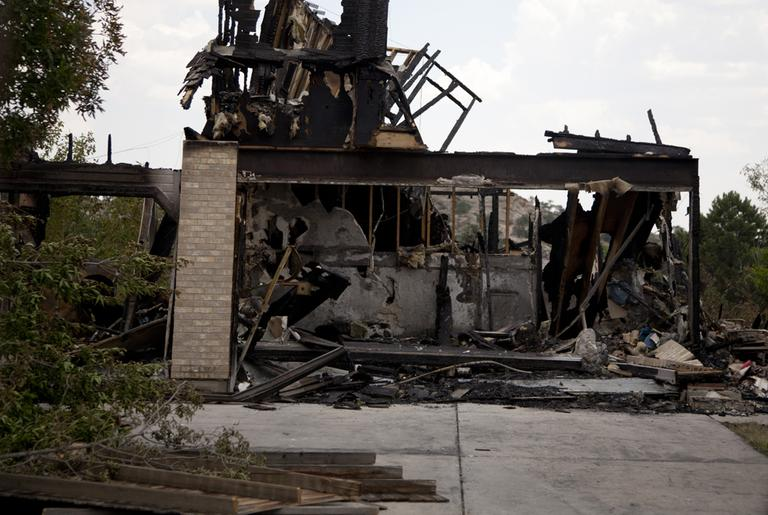 What is left of a burned home in the Mountain Shadow neighborhood, devastated by raging wildfires, Friday, June 29 in, Colorado Springs, Colo. (AP)