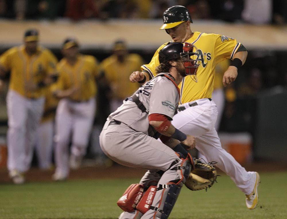 Oakland's Cliff Pennington scores the game winning run hit off  Red Sox catcher Jarrod Saltalamacchia last night in Oakland. Pennington scored on a sacrifice fly hit by Coco Crisp. (AP Photo)