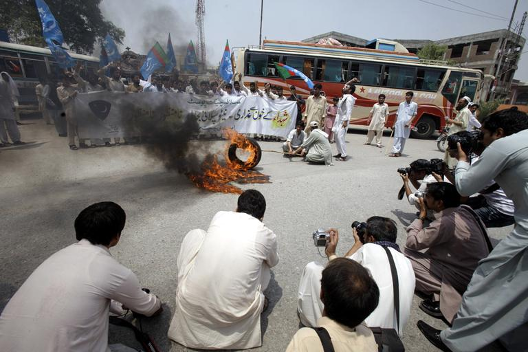 Pakistani students of Jamaat-i-Islami burn tire and rally to condemn the resumption of NATO supplies to neighboring Afghanistan through Pakistan, in Peshawar, Pakistan, Thursday, July 5. (AP)