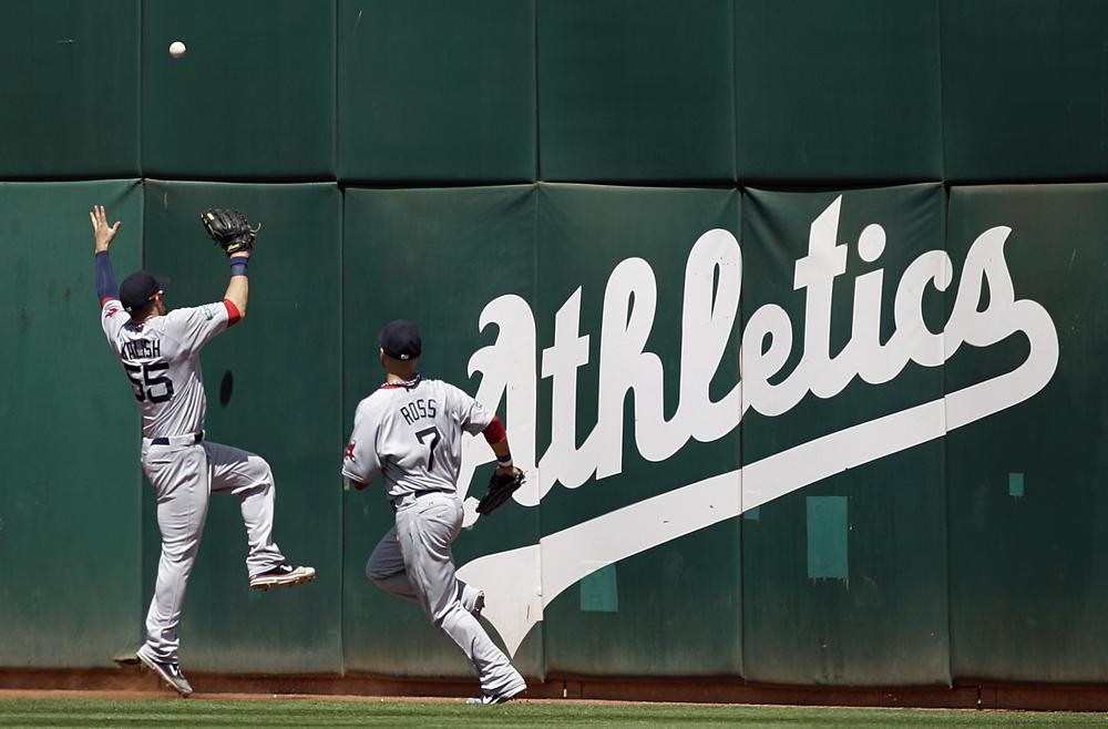 Red Sox outfielders Ryan Kalish, left, and Cody Ross fail to make the catch on a ball that fell for a triple hit by Oakland Athletics' Coco Crisp in the seventh inning of last night's game in Oakland. (AP Photo)