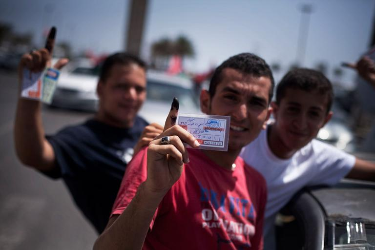 Libyan men hold their elections ID cards while celebrating election day in Tripoli, Libya on Saturday. (Manu Brabo/AP)