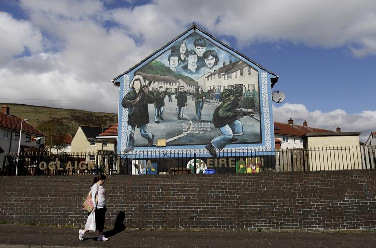 A woman walks past an Irish Republican Army mural in West Belfast, Northern Ireland. A U.S. appeals court ruled that interviews given by former IRA members must be handed over to the Police Service of Northern Ireland. The interviews are part of the Boston College Belfast Project which began in 2001 and lasted five years. (AP)
