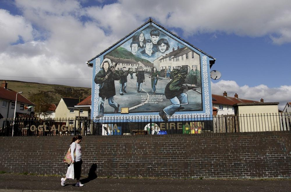 A woman walks past an Irish Republican Army mural in West Belfast, Northern Ireland, Wednesday, April, 4, 2012.  A U.S. appeals court ruled that interviews given by former IRA members must be handed over to the Police Service of Northern Ireland.  The interviews are part of the Boston College Belfast Project which began in 2001 and lasted five years. (AP)