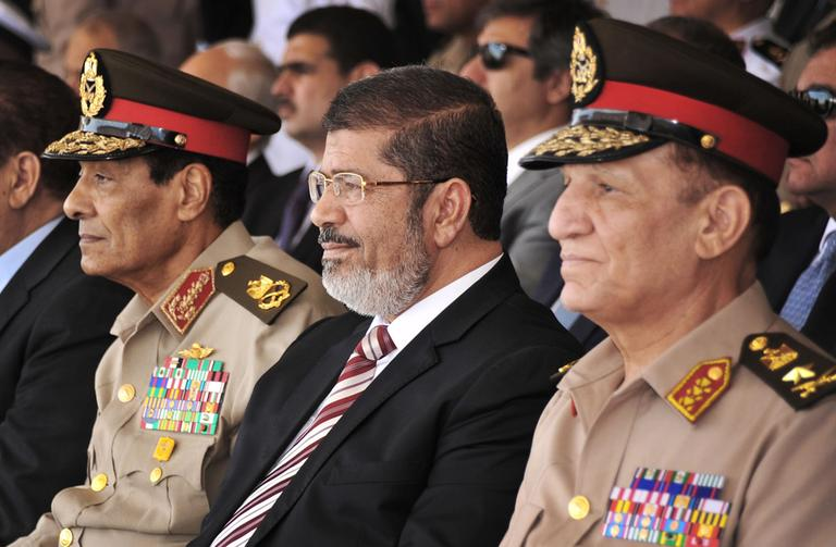 Egyptian Field Marshal Gen. Hussein Tantawi, left, and new President Mohammed Morsi, center, attend a medal ceremony, at a military base east of Cairo, Egypt. (AP/Mohammed Abd El Moaty, Egyptian Presidency)