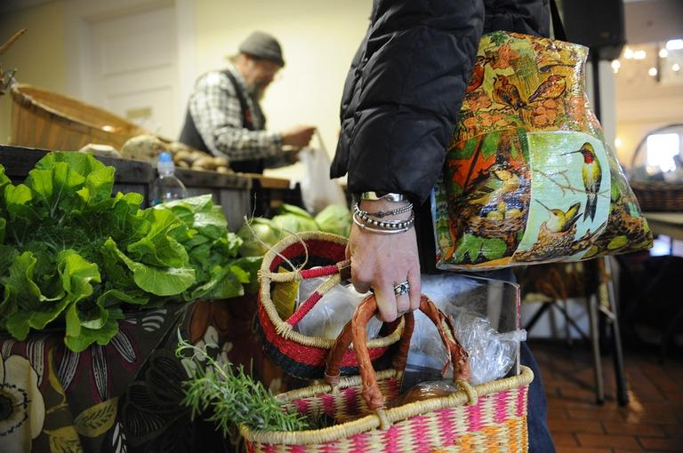 In this photo taken Dec. 9, 2010, Joani Gwilliam, of Plymouth, Mass., holds bags full of herbs and produce while making a stop at one of the many indoor farm stands inside the visitor center at Plimouth Plantation in Plymouth, Mass. (AP)