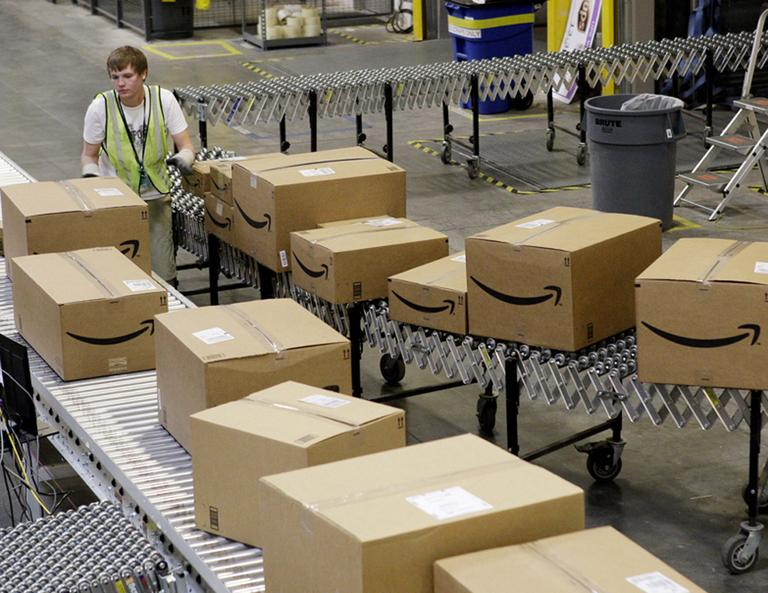 A worker separates packages for final shipment inside the 800,000 sq. ft. Amazon.com warehouse in Goodyear, Ariz. (AP)
