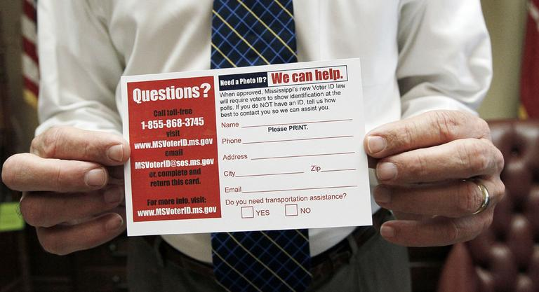 Mississippi Secretary of State Delbert Hosemann holds a postcard to help identify voters in need of a free state government issued card that is issued through his office at no charge, in Jackson, Miss. (AP)