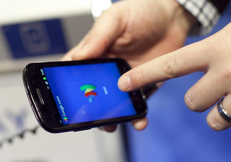 A person tries a smartphone loaded with Google Wallet at the National Retail Federation, Tuesday, Jan. 17, 2012 in New York. (AP)