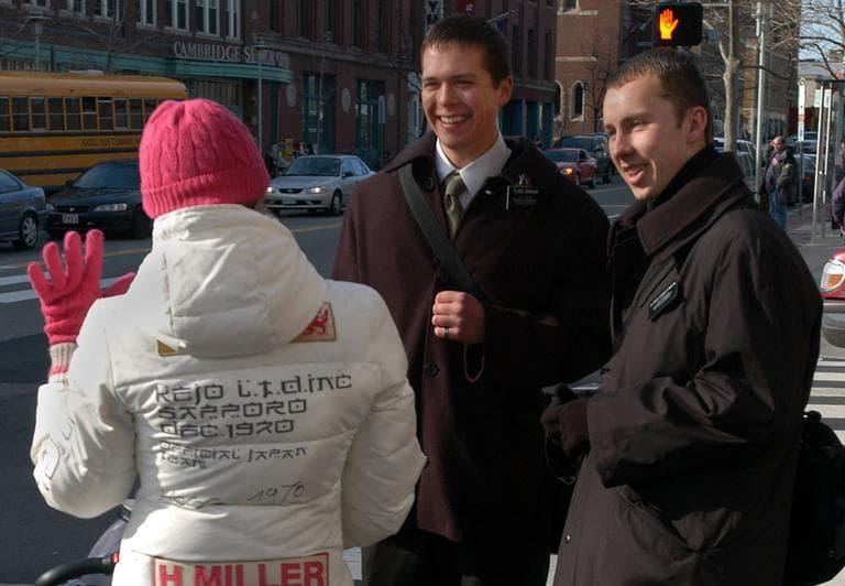 Mormon missionaries Cameron Johnson, center, and Jeremy Christenson, right, greet a pedestrian in Cambridge, Mass. (AP)