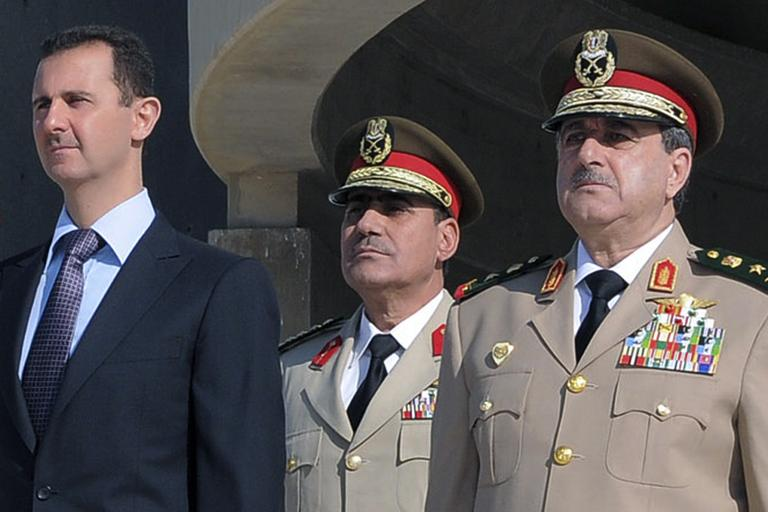 In this Thursday Oct. 6, 2011 photo released by the Syrian official news agency SANA, Syrian President Bashar Assad, left, stands next to Syrian Defense Minister Gen. Dawoud Rajha, right, during a ceremony to mark the 38th anniversary of the October 1973 Arab-Israeli war, in Damascus, Syria. Syria's state-run TV says the country's defense minister has been killed in a suicide blast in the capital. Wednesday's attack struck the National Security building in Damascus during a meeting of Cabinet ministers and senior security officials. (AP)