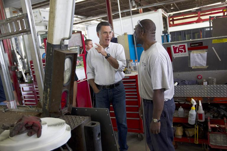 Mitt Romney, left, talks with Rodney Hollis, an employee of Middlesex Truck and Coach, during a campaign stop on Thursday in Roxbury. (AP)