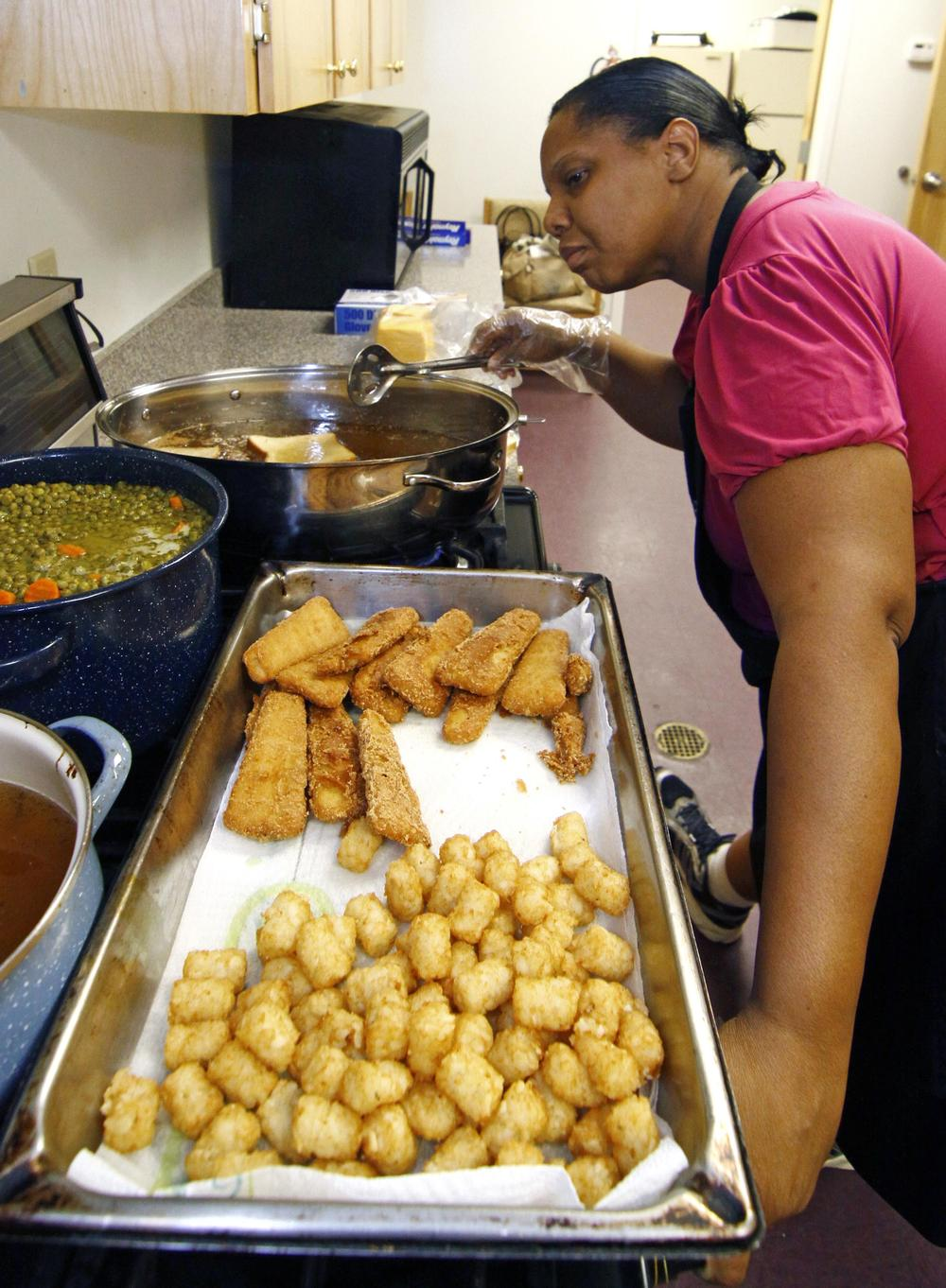 Earnestine Nelson, chief cook for the Alpha and Omega Church's free summer meals program for children and teens, checks the progress of her peas and carrots while frying fish fillets and tater tots for lunch in Jackson, Miss. (AP)