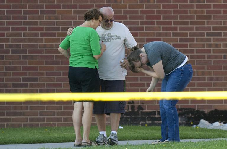 Tom Sullivan, center, stands with family members outside Gateway High School where witness were brought for questioning after a gunman opened fire at the midnight premiere of The Dark Knight Rises Batman movie Friday in Aurora, Colo. (AP)