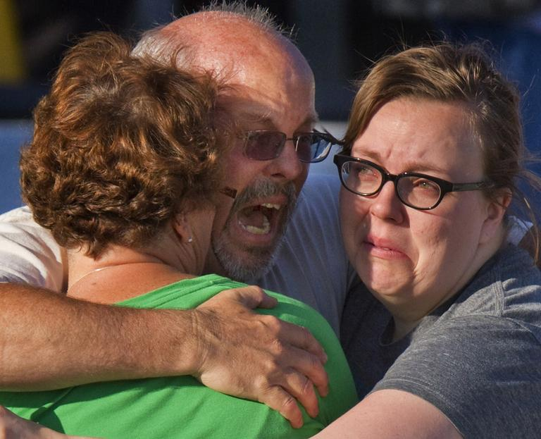 "Tom Sullivan, center, embraces family members outside Gateway High School where he has been searching franticly for his son Alex Sullivan who celebrated his 27th birthday by going to see ""The Dark Knight Rises,"" movie where a gunman opened fire Friday, in Aurora, Colo. (AP)"