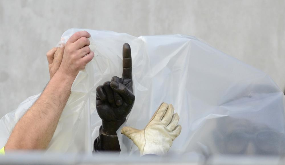 Workers handle the statue of former Penn State football coach Joe Paterno before removing the statue Sunday. (AP)
