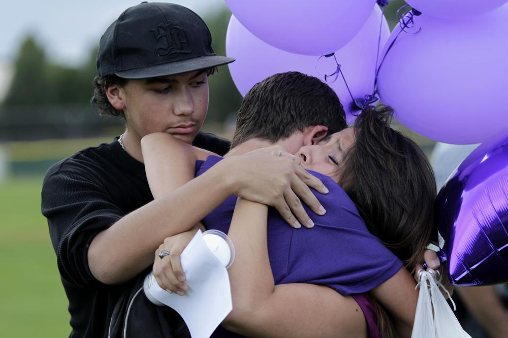 Students comfort each other Saturday, during a vigil at Gateway High School in Aurora, Colo., for AJ Boik, who was a student at the school and who was killed along with 11 others when a gunman opened fire in a movie theater. (AP)