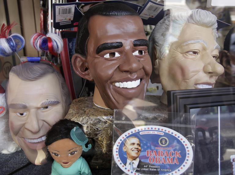 Life-sized masks meant to resemble U.S. presidents, from the left, George W. Bush, Barack Obama, and Bill Clinton, appear in a store-front window, in the downtown section of Oak Bluffs, Mass. (AP)