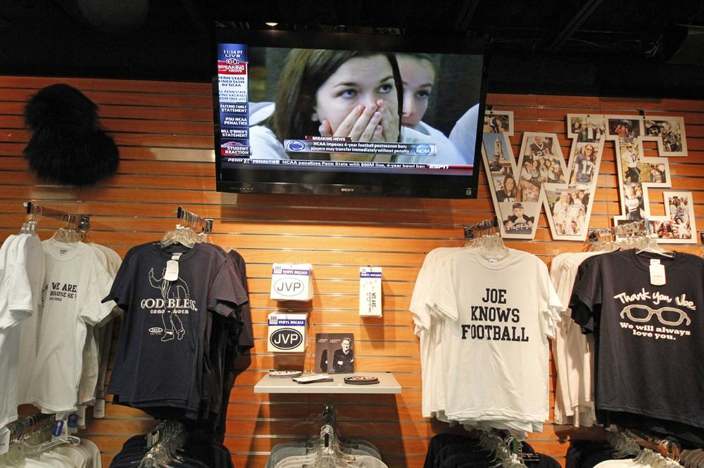 T-shirts supporting Joe Paterno hang in a downtown State College, Pa., shop as an ESPN report on the NCAA sanctions plays on the television Monday, July 23, 2012.(AP Photo)