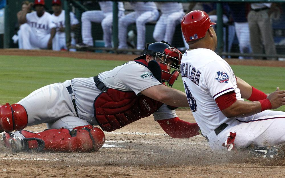 Rangers' Yorvit Torrealba is tagged out sliding into home by Red Sox catcher Kelly Shoppach during the third inning in Arlington, Texas. (AP)