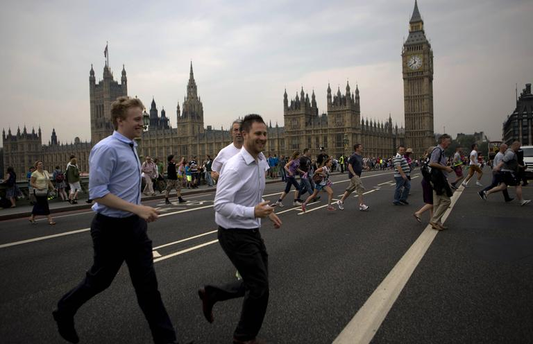People cross the Westminster bridge to watch the royal barge Gloriana carry the Olympic flame along the river Thames, ahead of the 2012 Summer Olympics, on the final day of the Torch Relay, Friday. (AP)