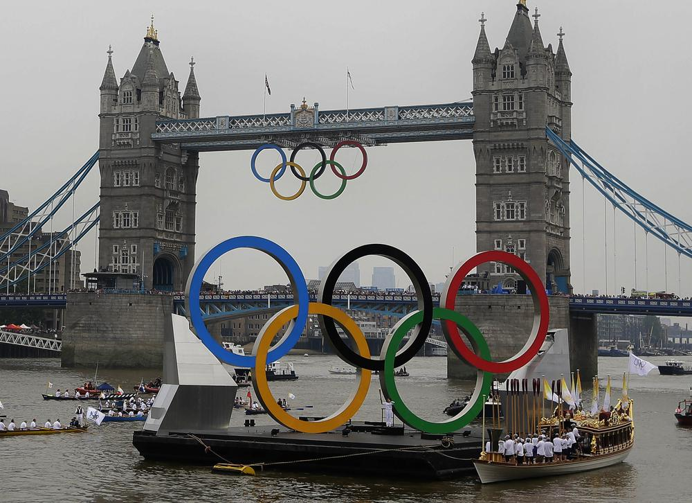 The royal barge Gloriana carries the Olympic flame along the river Thames on the final day of the Torch Relay, Friday, in London. (AP)