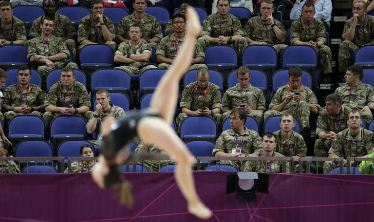 British soldiers watch gymnast Simona Castro Lazo from Chile perform during the Artistic Gymnastics women's qualification at the 2012 Summer Olympics, Sunday in London. Troops, teachers and students are getting free tickets to fill prime seats that were empty at some Olympic venues on the first full day of competition. (AP)