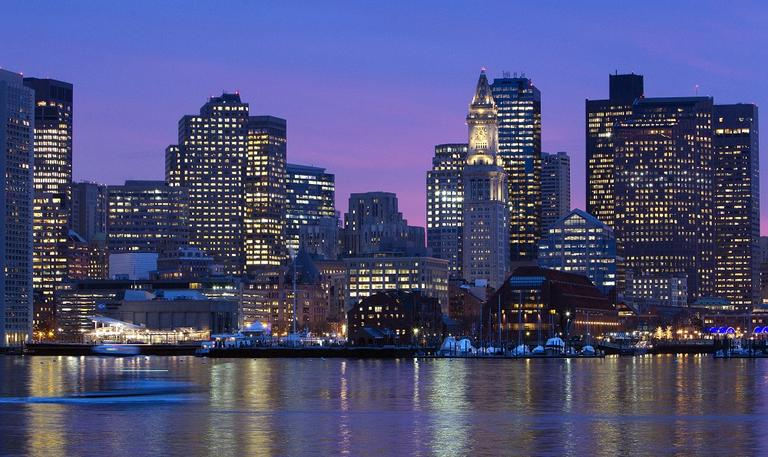 The city skyline is seen at dusk on the Boston Harbor. (AP)