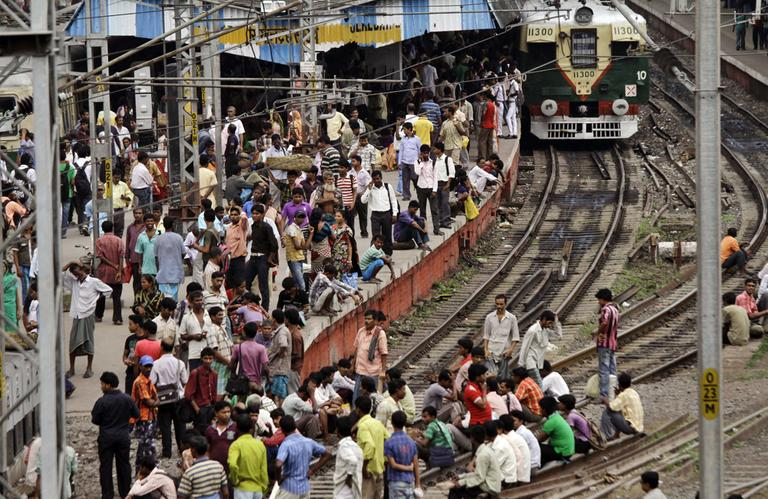 Indian stranded passengers wait for the train services to resume following a power outage at Sealdah station in Kolkata, India, Tuesday. (AP)