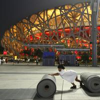 A child rolls up a carpet in front the National Stadium known as 'Birds Nest' in Bejing, Wednesday, Aug. 13, 2008. The 'Bird's  Nest' will host the Track and Field event of the Beijing 2008 Olympics, which will start Aug. 15, 2008.(AP Photo/Anja Niedringhaus)