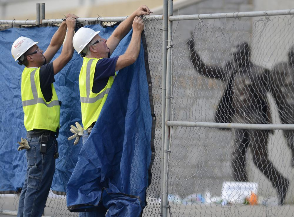 Workers place a tarp on a fence in front of the statue of Joe Paterno before removing it on Sunday, July 22, 2012, in State College, Pa. Yet another missed opportunity for Penn State? (AP Photo)