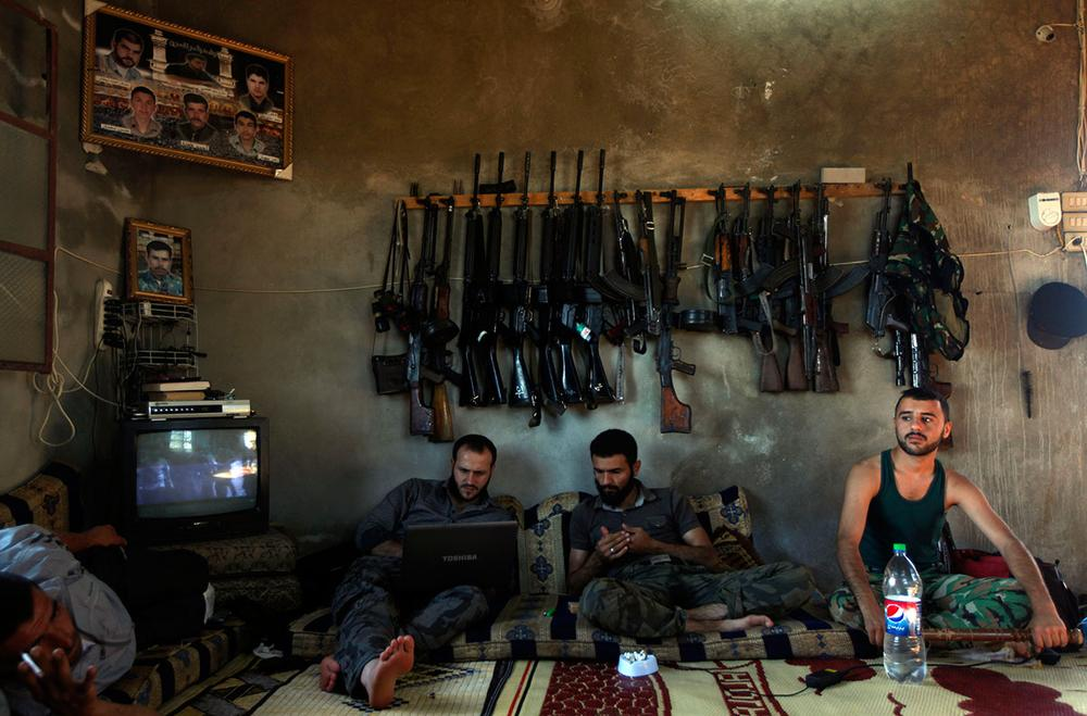 In this Tuesday, June 12, 2012 file photo, Free Syrian Army fighters sit in a house on the outskirts of Aleppo, Syria. During two weeks with rebels in northern Syria, three Associated Press journalists found more than 20 rebel groups who often destroy government army posts and convoys but lack the weapons and unity to do more than gradually chip away at the regime of President Bashar Assad _ a recipe for a long, bloody insurgency. (AP Photo/Khalil Hamra, File)