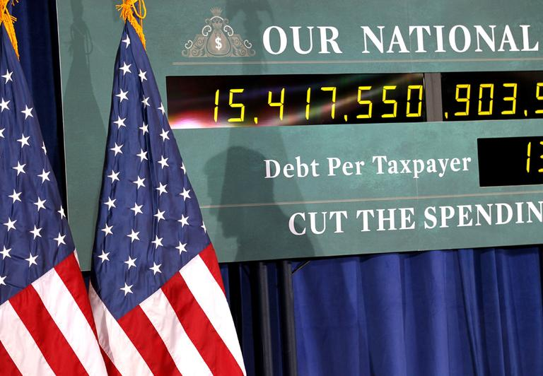The shadow of Republican presidential candidate, former Massachusetts Gov. Mitt Romney, is seen on a representation of the National Debt Clock as he speaks at a town hall meeting in Kalamazoo, Mich., Friday, Feb. 24, 2012. (AP)