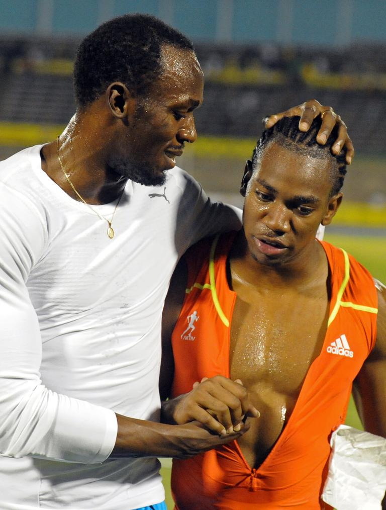 World champion Yohan Blake, right, is congratulated by world-record holder Usain Bolt after Blake defeated Bolt in the 100m final at Jamaica's Olympic trials in Kingston, Jamaica in June. (AP)