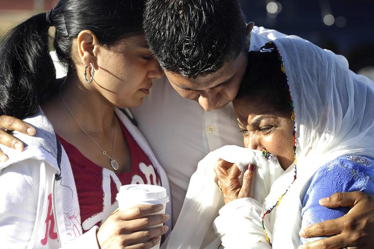 Amardeep Kaleka, son of the president of the Sikh Temple of Wisconsin, center, comforts members of the temple in Oak Creek, Wis., where a gunman killed six people a day earlier, before being shot and killed himself by police. (AP)