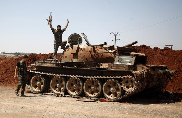 A Free Syrian Army fighter waves from the top of a destroyed army tank in the town of Anadan on the outskirts of Aleppo, Syria on Monday. (AP Photo/Khalil Hamra)