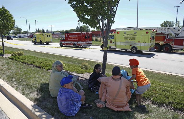Bystanders sit in the shade at the scene of a shooting inside a Sikh temple in Oak Creek, Wis., Sunday, Aug. 5, 2012. (AP)