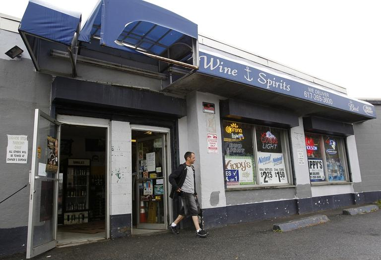 A passer-by departs a liquor store in Boston's South Boston neighborhood, on Thursday, June 23, 2011. (AP)