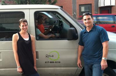 Dana Betts, Roca's director of programming, and Chelsea Police Lt. Ed Conley stand beside the Roca van. Youth workers Zac Rich, near, and Tha Thai sit inside the van. (Deborah Becker/WBUR)