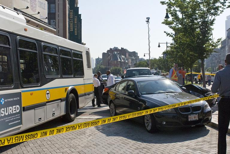 An off-duty MBTA bus pushed two vehicles into the median in Kenmore Square during an accident Thursday morning. (Josh Berlinger for WBUR)