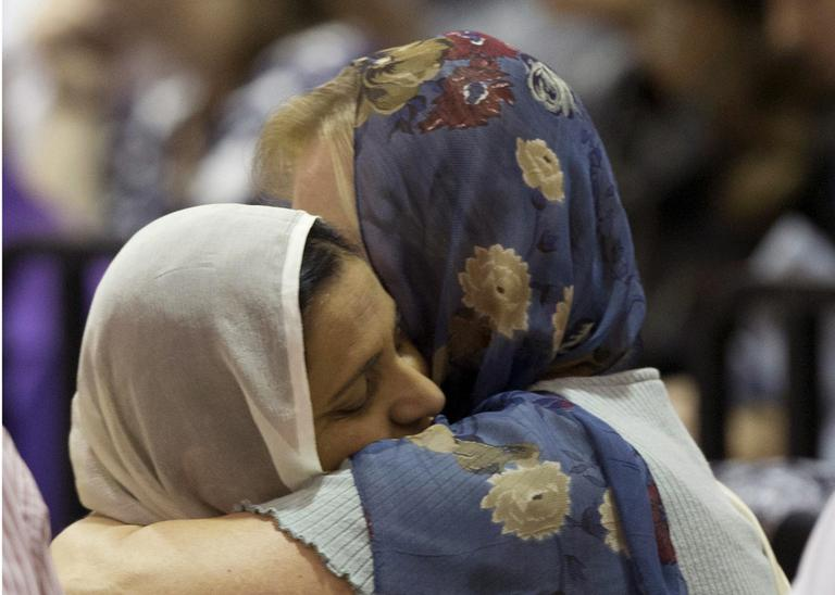 Mourners console one another at the funeral and memorial service for the six victims of the Sikh temple of Wisconsin mass shooting in Oak Creek, Wis., Friday, Aug 10, 2012. (AP)