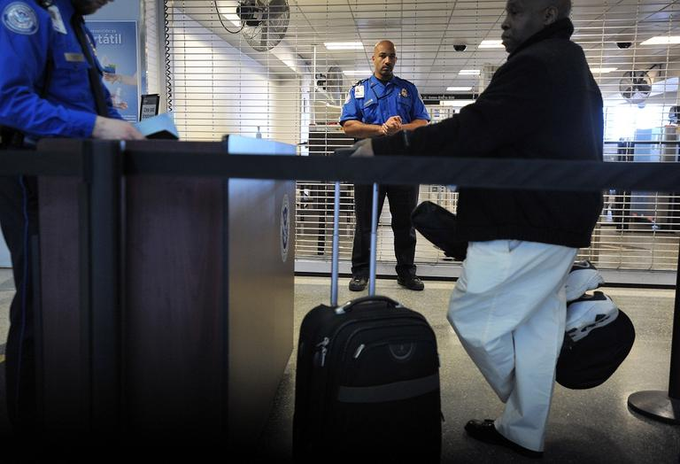 A TSA employee being trained in Behavioral Pattern Recognition watches passengers in line at a security checkpoint at Logan Airport in Boston, in 2010. (AP/Josh Reynolds)