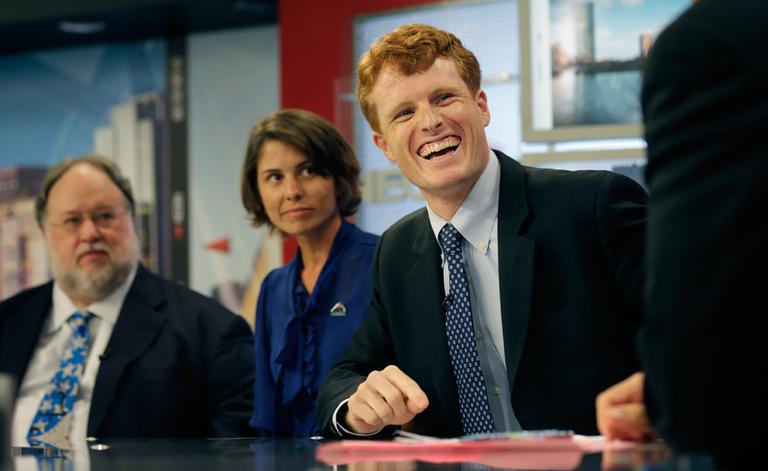 Joseph Kennedy III, right, laughs while listening to NECN host Jim Braude during a candidate's debate for the 4th Congressional District Thursday. With Kennedy are Herb Robinson and Rachel Brown. (AP)