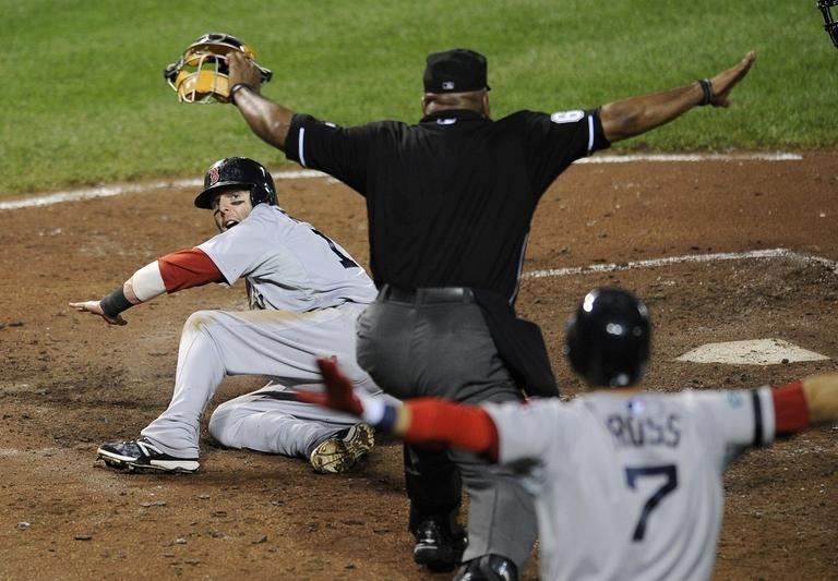 """Red Sox's Dustin Pedroia, left, looks up as home plate umpire Laz Diaz, center, and Red Sox's Cody Ross (7) signal """"safe"""" as while scoring on a sacrifice fly by Adrian Gonzalez on Thursday. (AP/Nick Wass)"""
