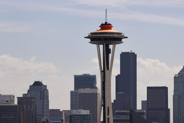 """The top of the Space Needle sports a new coat of orange, called """"galaxy gold"""" when it first appeared 50 years ago atop the structure, as part of the landmark's 50th anniversary celebration Monday, April 23, 2012, in Seattle. The Space Needle, 605 feet tall, officially opened on the first day of the World's Fair April 21, 1962. (AP)"""
