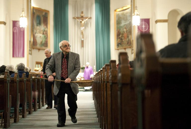 John Alves, of Dartmouth, Mass., uses a basket while taking collection during Mass at St. John the Baptist Church in New Bedford, Mass. in 2009. (AP)